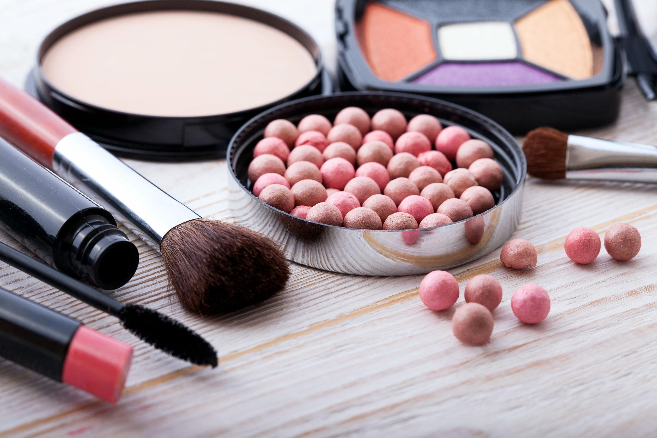 Productos cosméticos de maquillaje sobre fondo de madera blanco