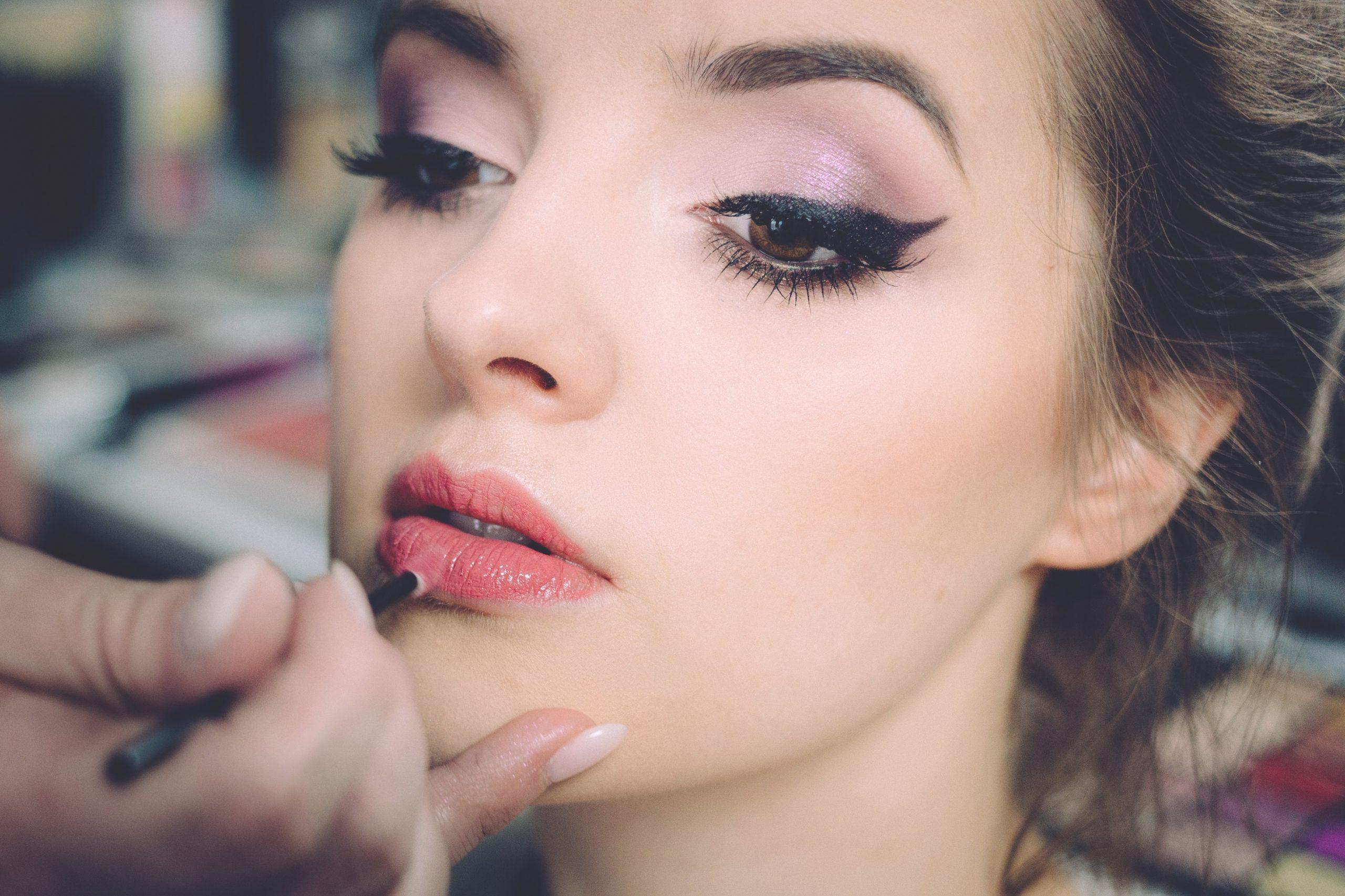 Mujer aplicándole lápiz labial