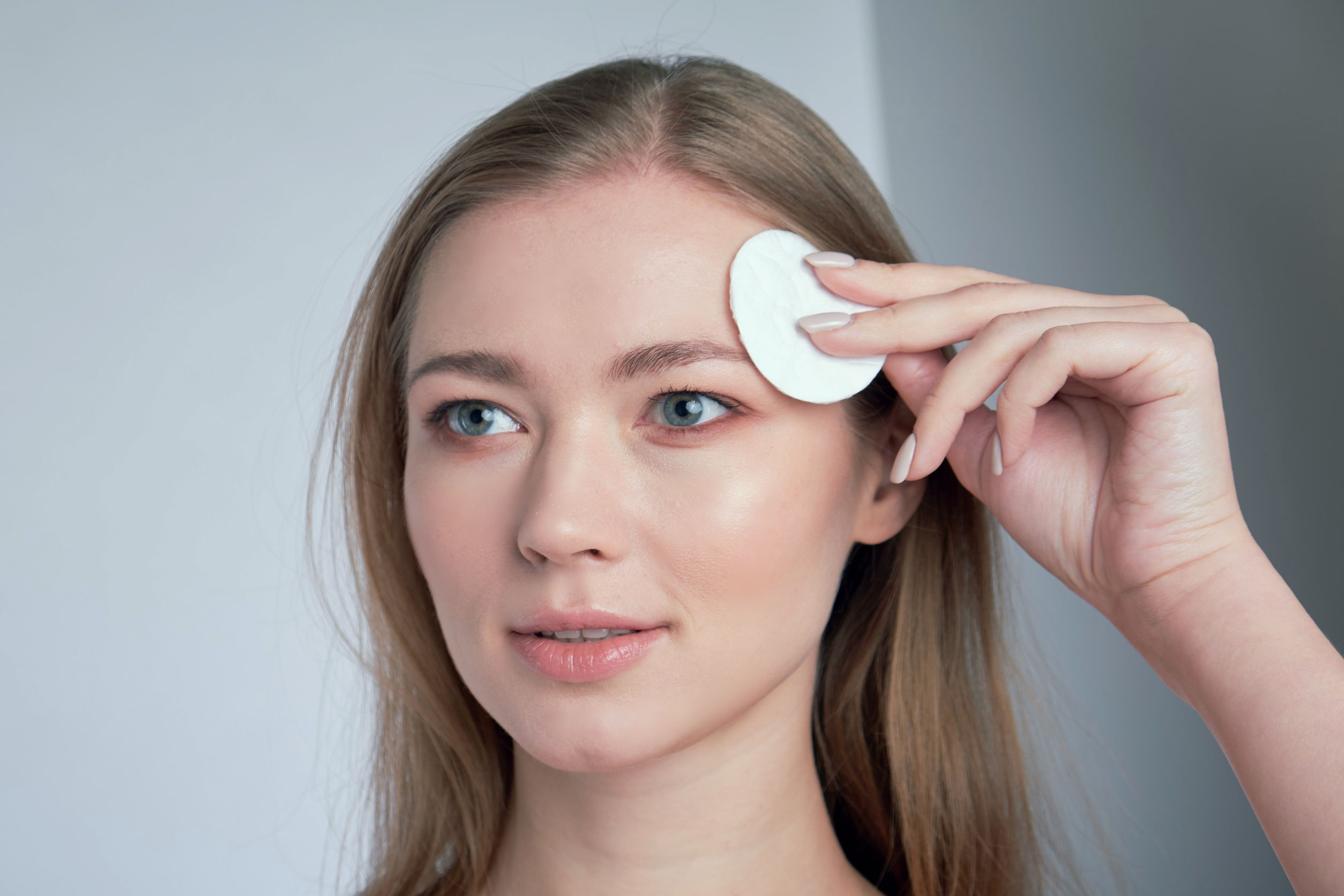una mujer limpiandose la cara frente al a e lje