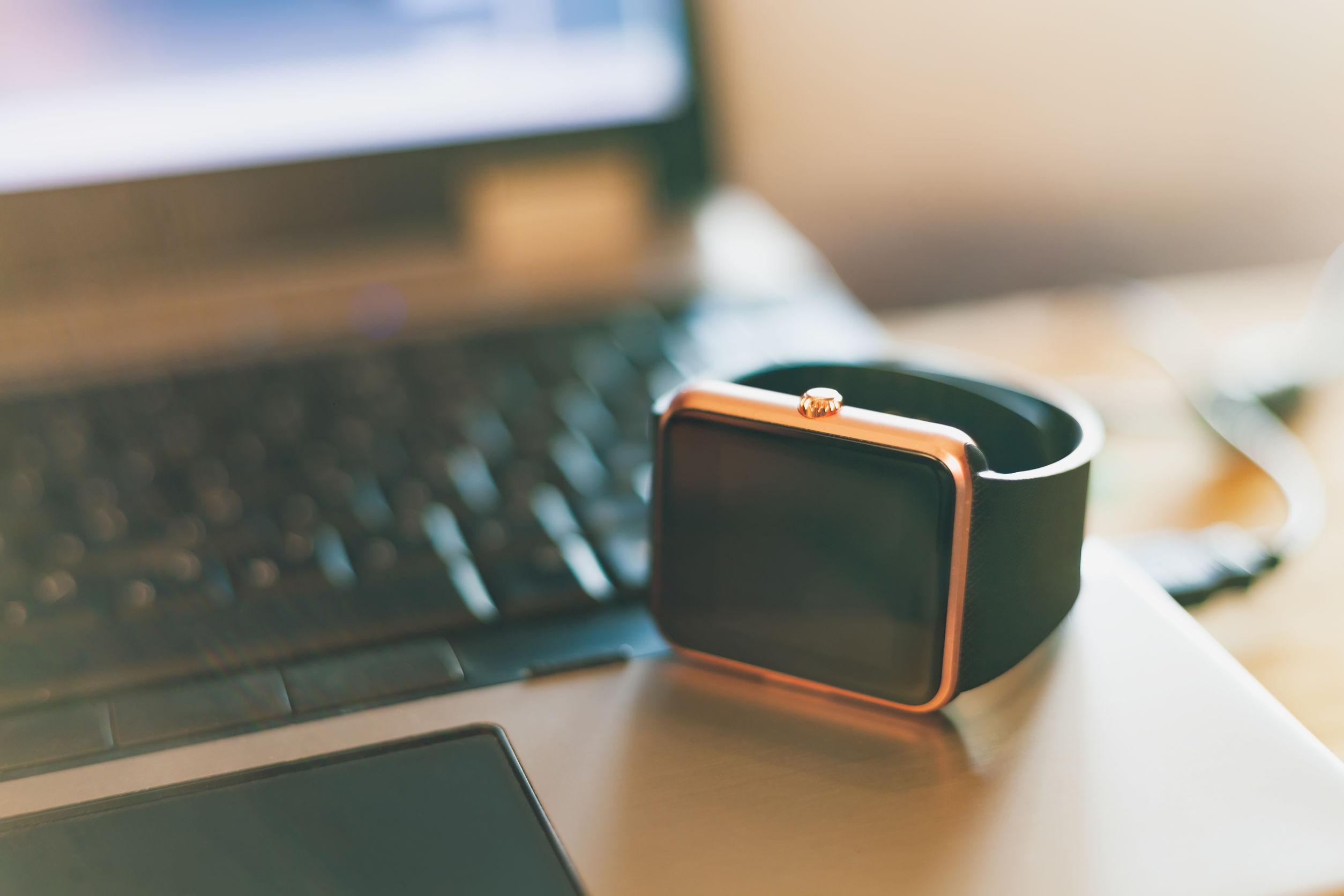 Reloj de pulsera elegante moderno que sobre notebook