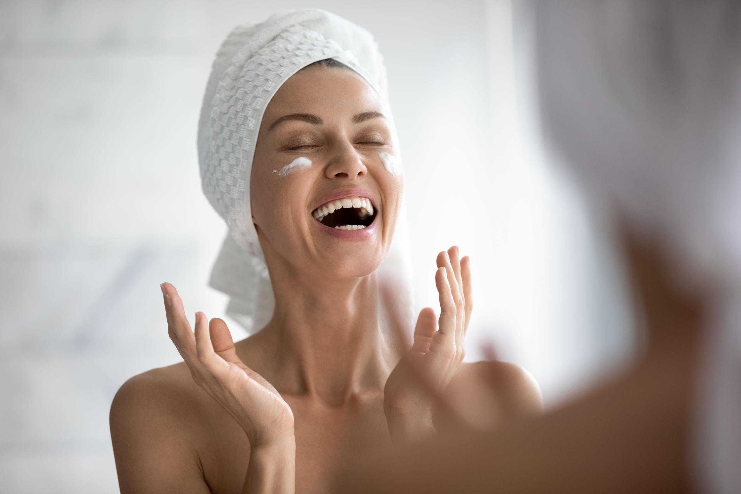 Mujer joven divertida positiva riendo mientras se aplica la crema facial reflejándose en el espejo