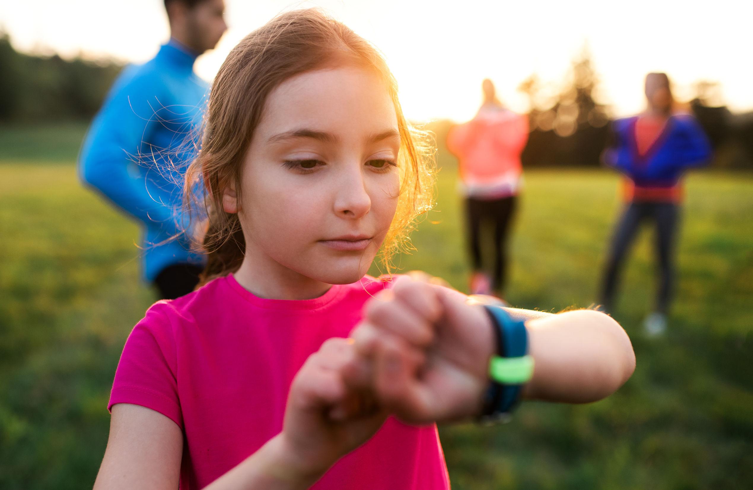 una niña pequeña con un gran grupo de personas que hacen ejercicio en la naturaleza