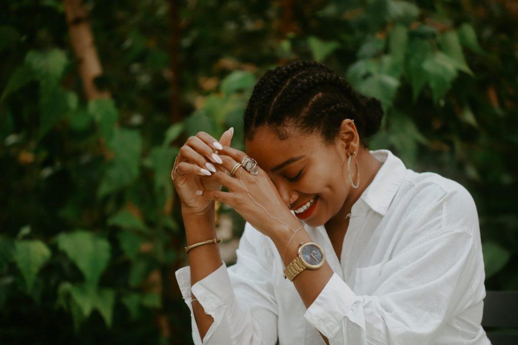 Mujer sonriendo portando reloj en mano izquierda