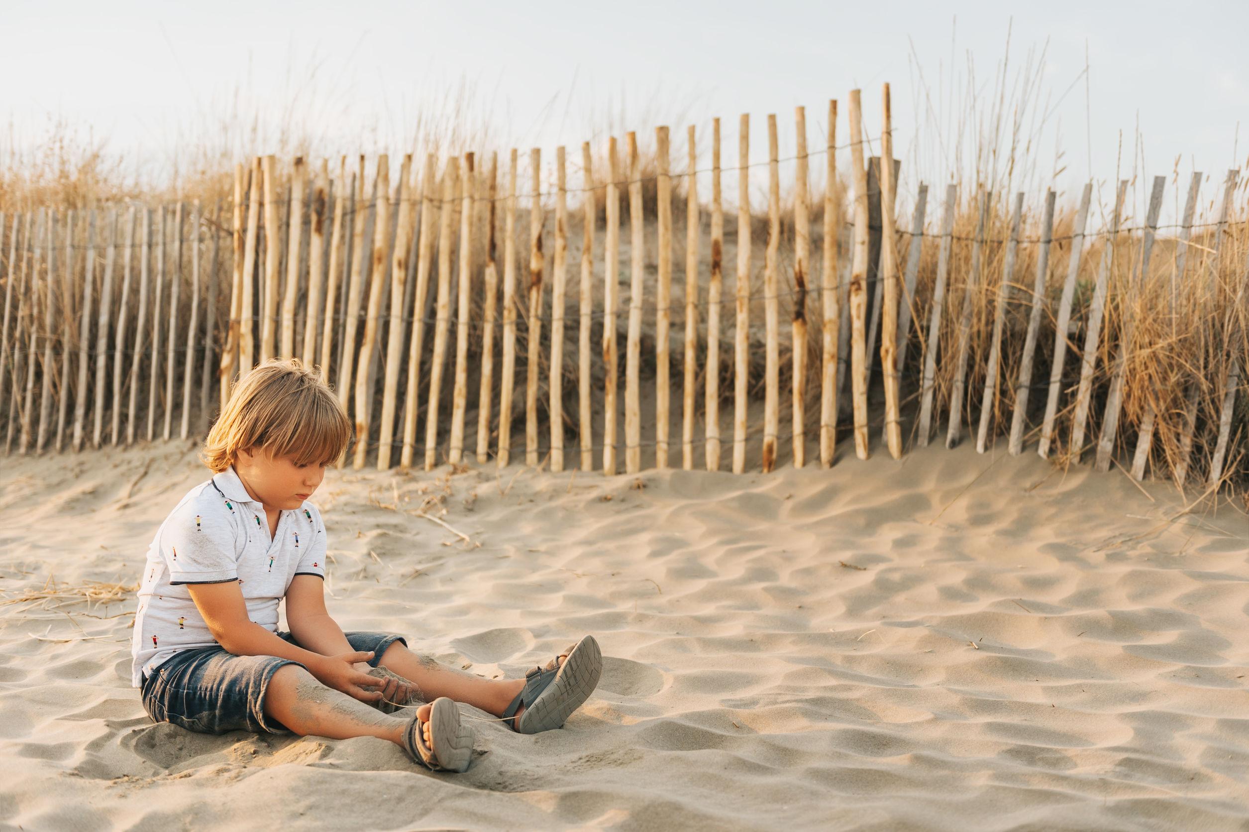 niño descansando en la playa de arena junto al mar al atardecer