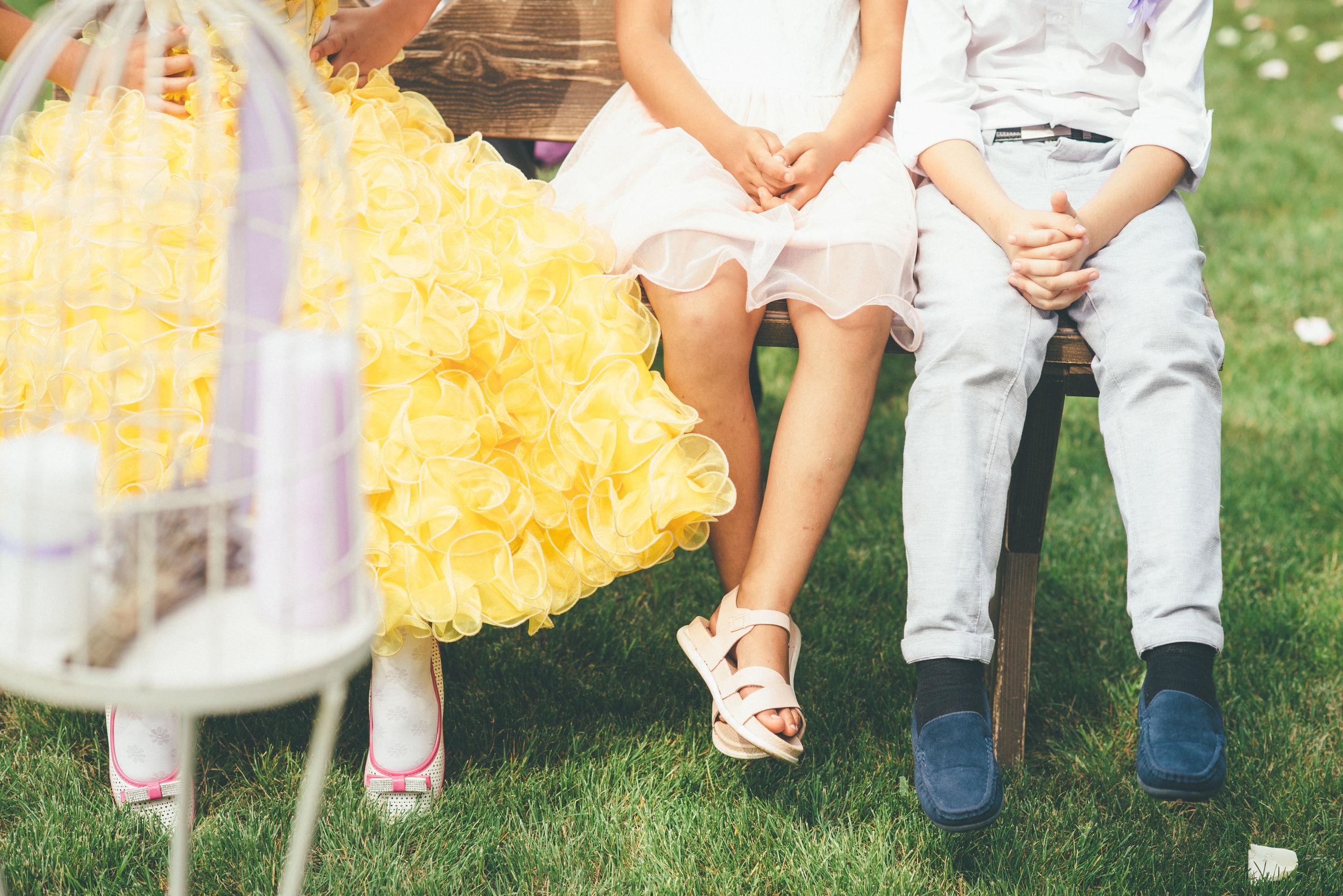 Tres niños vestidos de fiesta, sentados en un banco, una niña tiene un vestido amarillo muy atractivo y sandalias.